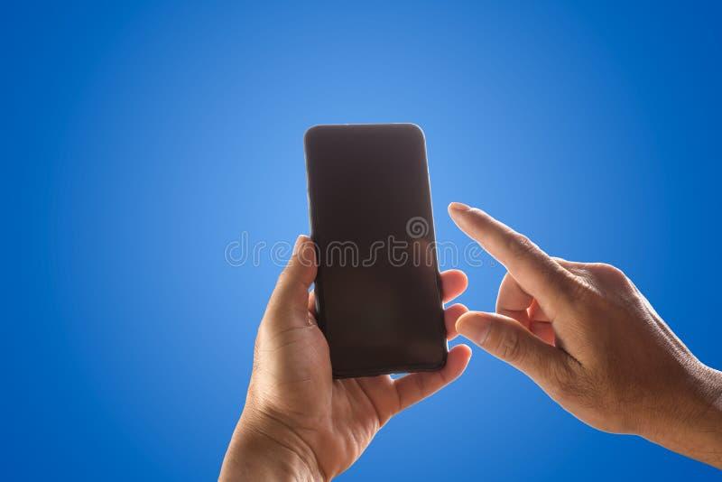 递拿着电话在蓝色隔绝的流动和触摸屏 免版税库存照片