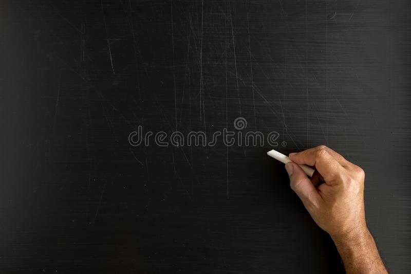 递拿着白垩和写某事反对黑板wi 库存照片