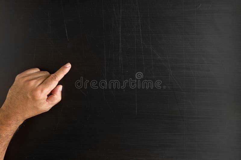 递拿着白垩和写某事反对黑板wi 免版税库存照片