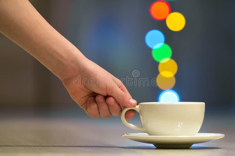 递拿着白色咖啡与五颜六色的bokeh蒸汽的 库存照片