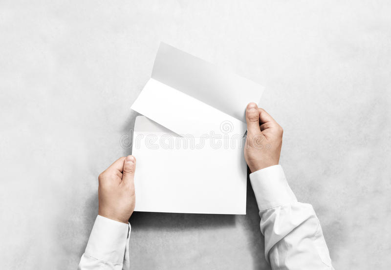 递拿着白色空白的信封和被折叠的传单大模型,被隔绝 免版税库存照片