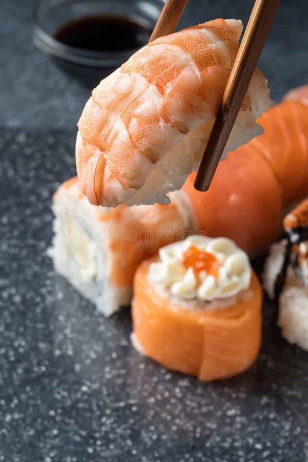 递拿着筷子寿司用在灰色背景的虾  图库摄影