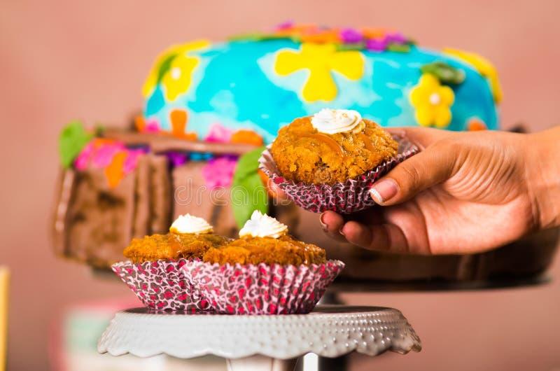 递拿着褐色的可口松饼,大五颜六色的蛋糕在背景,酥皮点心概念中 免版税库存图片