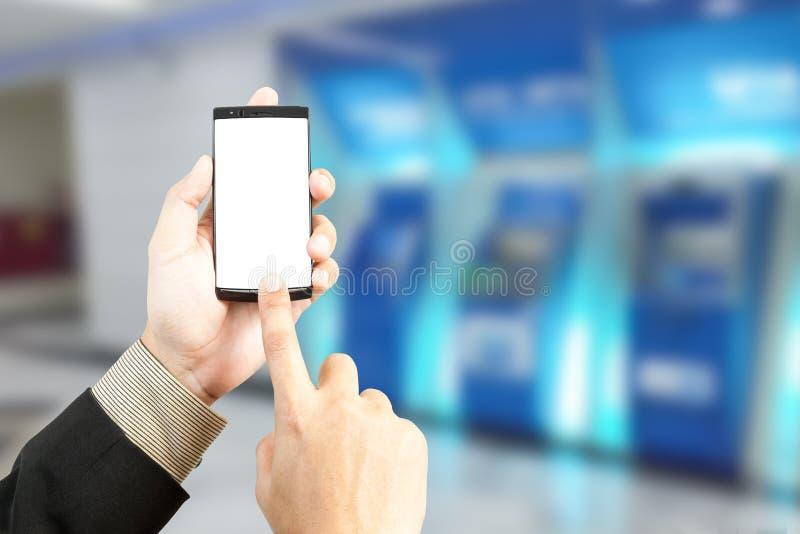 递拿着调动银行业务的智能手机与迷离backgroun 图库摄影