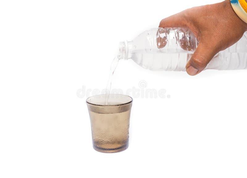 递拿着饮用水涌入一杯的瓶水 免版税图库摄影