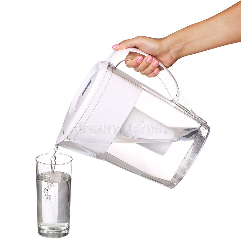 递拿着滤水器水罐和倾吐水入玻璃 免版税库存图片