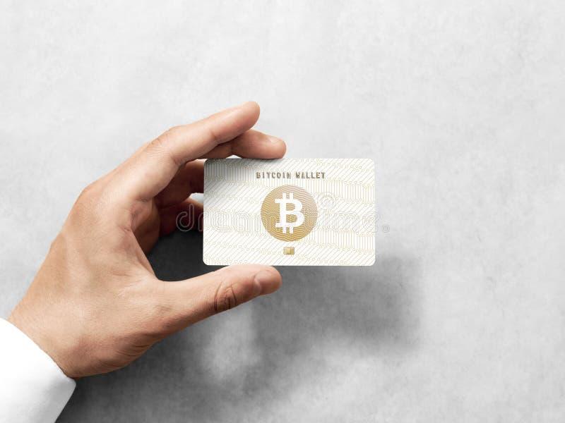 递拿着bitcoin与压印的金子商标的卡片模板 免版税库存图片