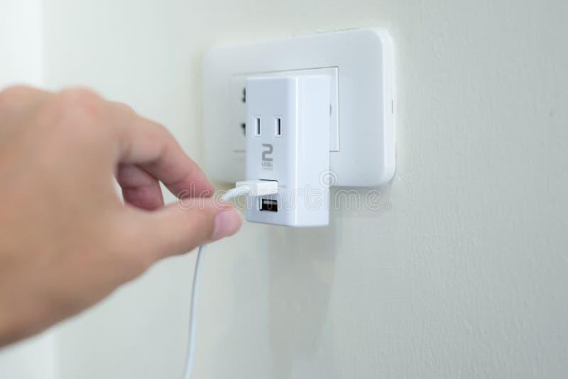 递拿着usb力量适配器充电器到电插口 库存图片