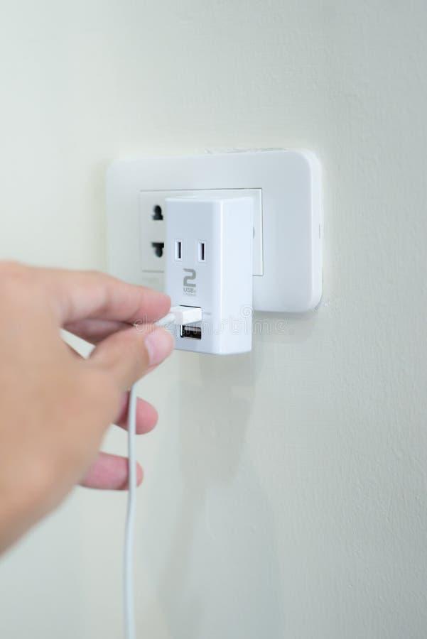 递拿着usb力量适配器充电器到电插口 免版税库存图片