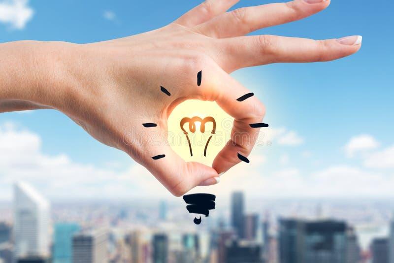 递显示与里面电灯泡的好标志,城市 免版税图库摄影