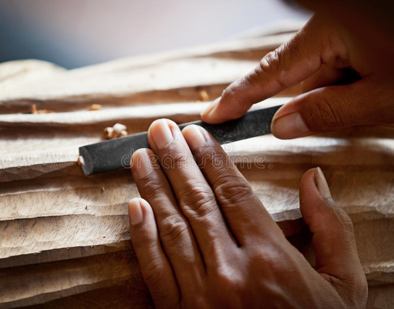 递有工具特写镜头的木雕家 库存图片