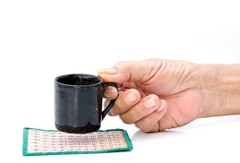 递有黑杯子的举行在白色桌上 免版税库存图片