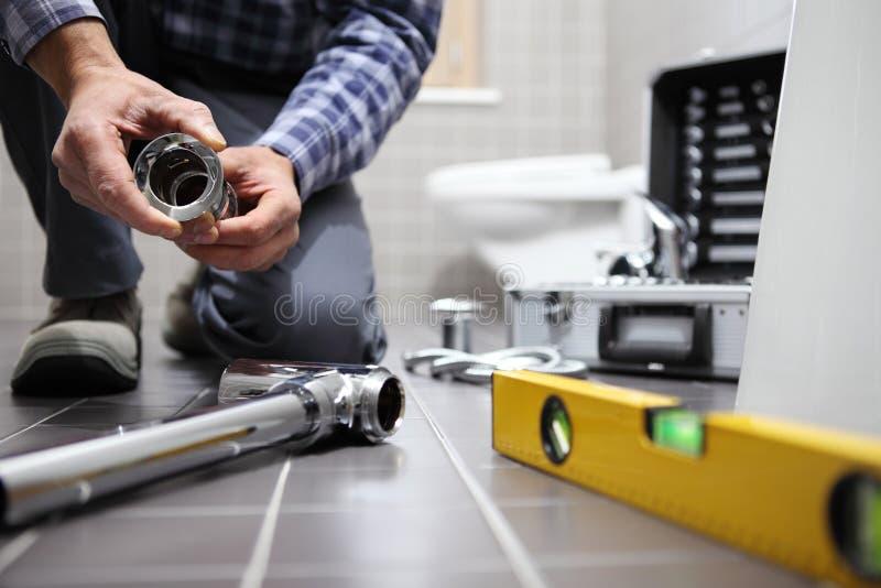 递水管工在工作在卫生间里,测量深度修理公司,  库存照片