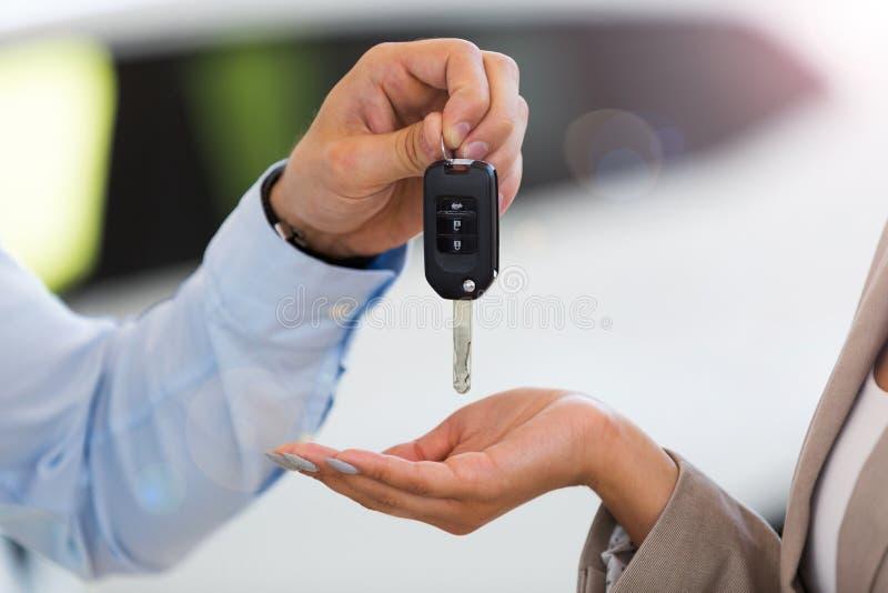 递汽车钥匙的汽车推销员对妇女 库存图片