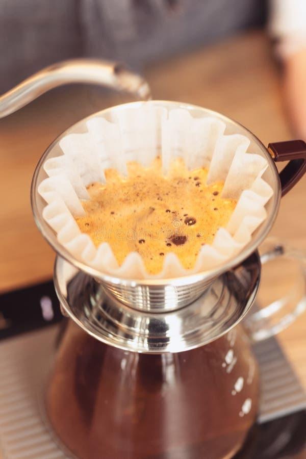 递滴水咖啡,在咖啡渣的Barista倾吐的水与过滤器 免版税库存图片