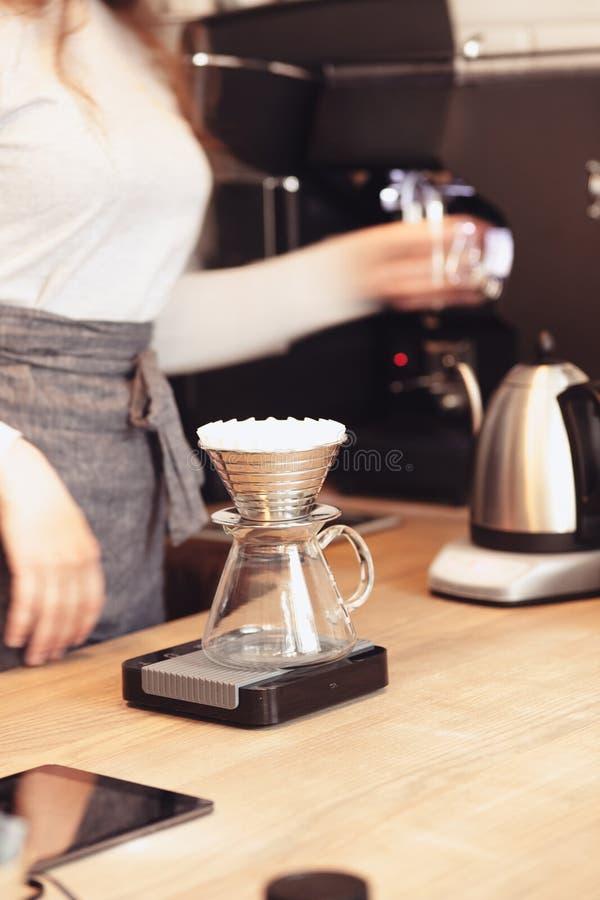 递滴水咖啡,在咖啡渣的Barista倾吐的水与过滤器 免版税库存照片