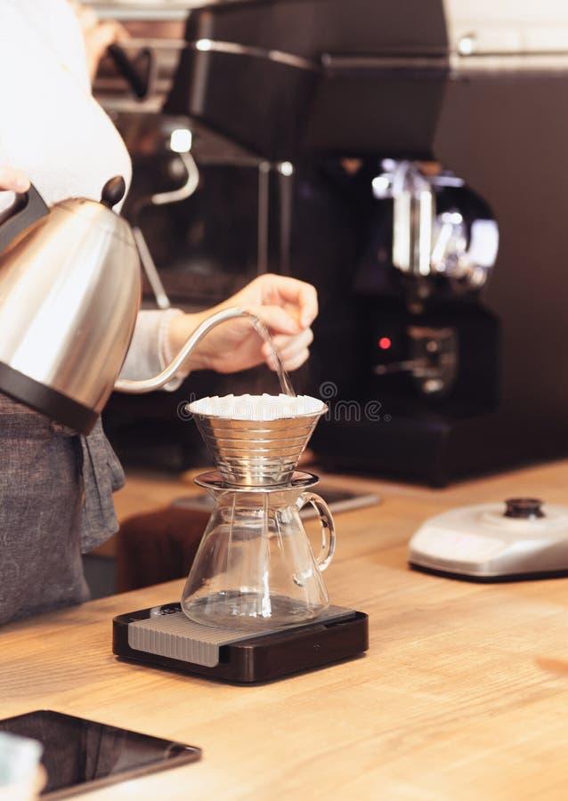 递滴水咖啡,在咖啡渣的Barista倾吐的水与过滤器 库存照片