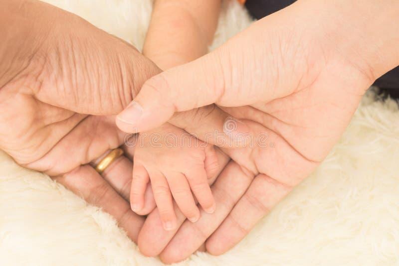 递睡觉的婴孩在母亲特写镜头(软的focu的手上 免版税库存照片
