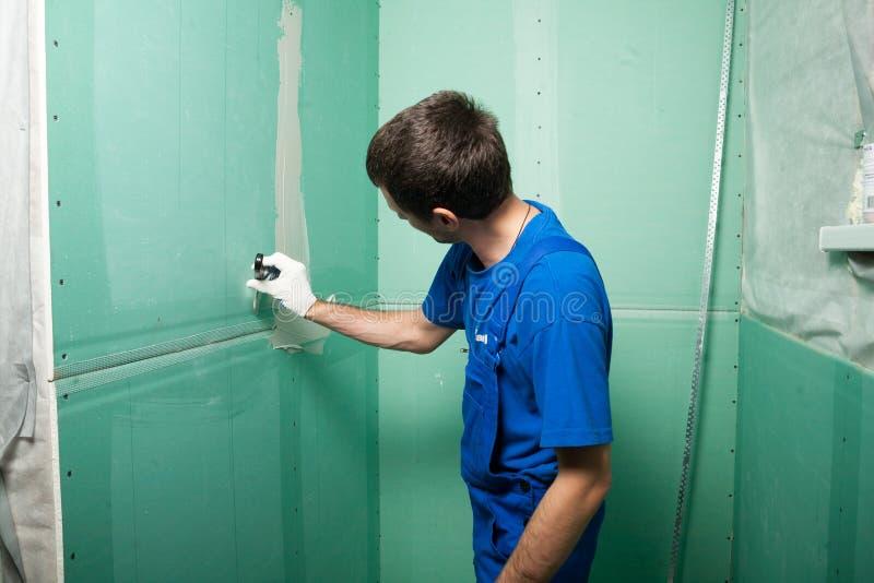 递石膏工在工作 膏药的应用在墙壁上的 免版税图库摄影
