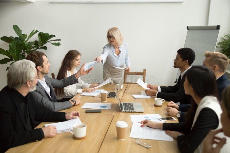 递财政报告的资深女实业家对经理在队 免版税库存图片