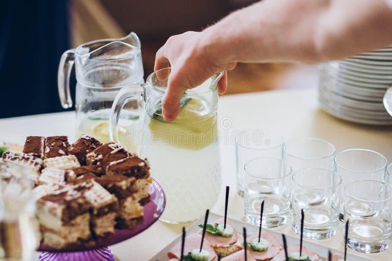 递采取杯新鲜的柠檬水在与drin的棒棒糖桌上 免版税库存图片