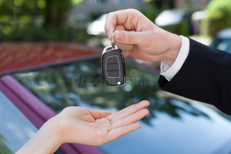 递钥匙的推销员对妇女乘新的汽车 免版税库存图片