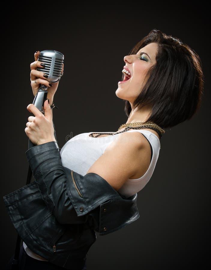 递mic的女性摇滚歌手 库存照片