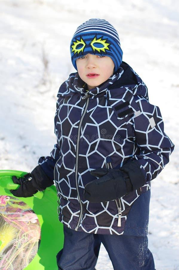 逗人喜爱儿童sledding 乘坐在雪的小孩男孩爬犁 免版税库存照片