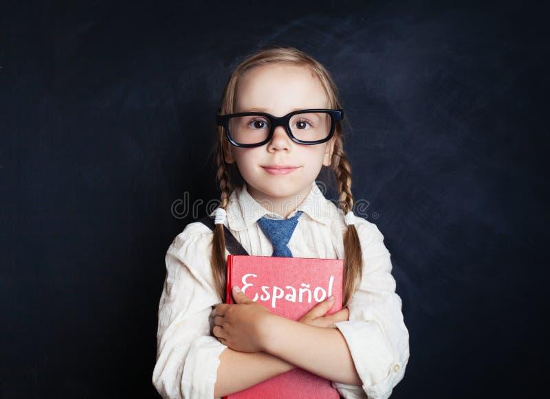 逗人喜爱反对黑板的儿童女孩拥抱西班牙书 免版税库存照片