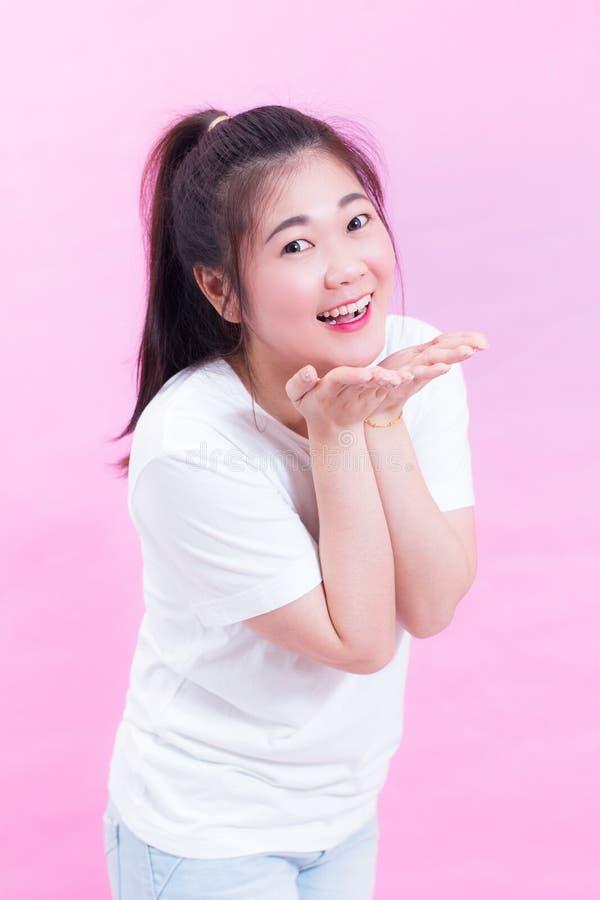 逗人喜爱可爱美好的年轻亚洲妇女黑发穿戴在桃红色背景的一个白色T恤杉身分和送亲吻 库存图片