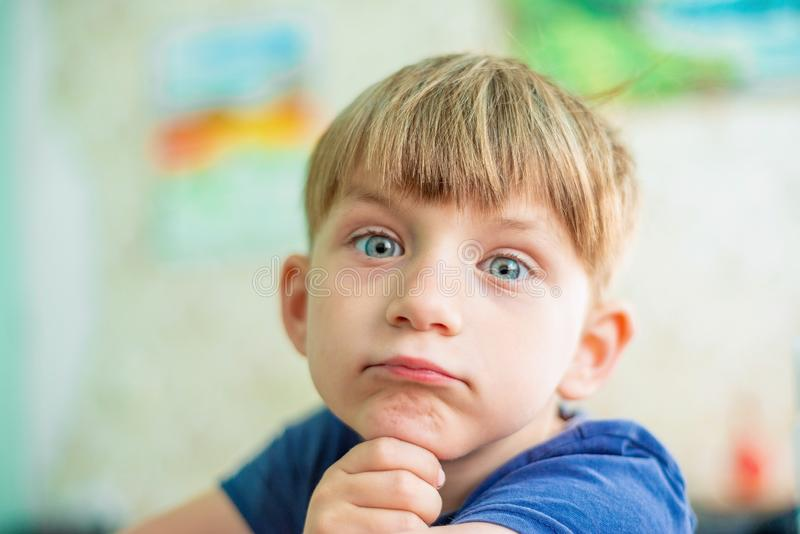 逗人喜爱和聪明的小男孩关闭的画象,是认为和看照相机 免版税库存照片