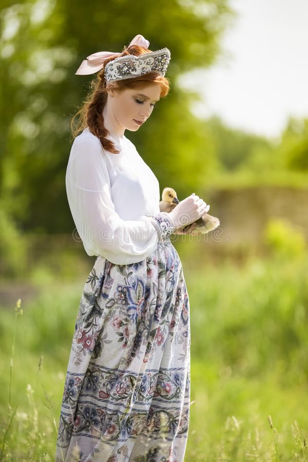 逗人喜爱和肉欲的时尚画象年轻白种人女性在手边摆在用鸭子 展示俄国样式礼服和 免版税图库摄影