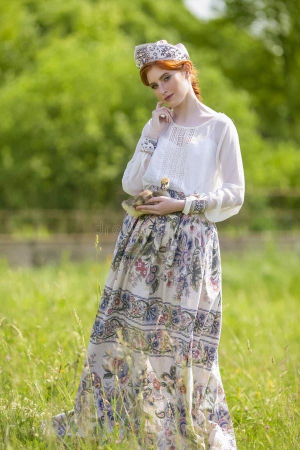 逗人喜爱和肉欲的时尚画象年轻白种人女性在手边摆在用鸭子 展示俄国样式礼服和 库存图片