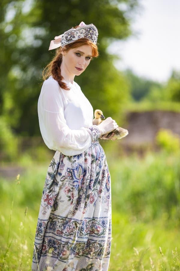 逗人喜爱和肉欲的时尚画象年轻白种人女性在手边摆在用鸭子 展示俄国样式礼服和 免版税库存图片