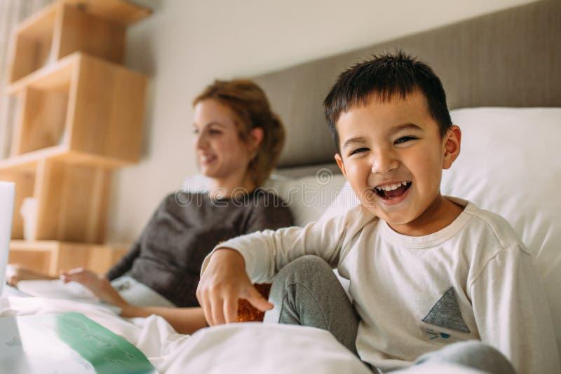 逗人喜爱在床上的小男孩与母亲在后面 免版税库存照片