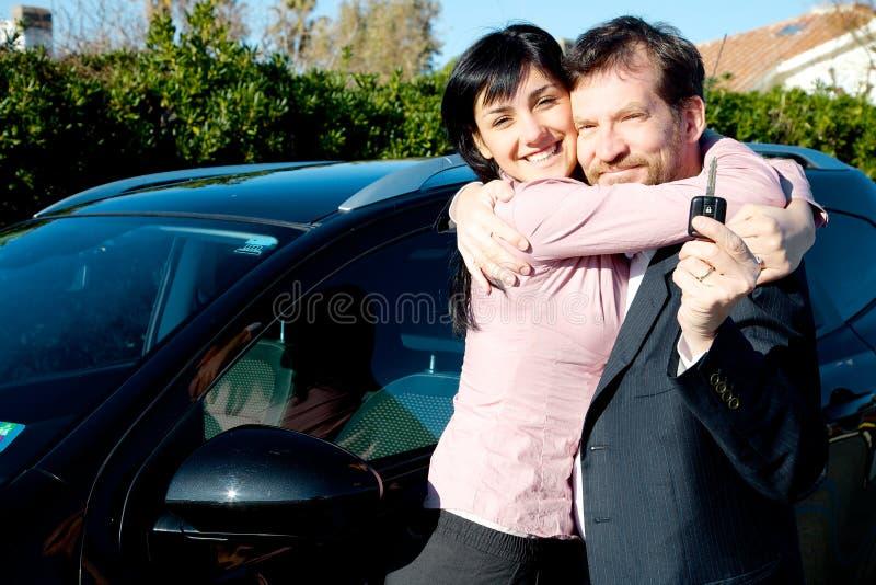 逗人喜爱夫妇拥抱愉快为新的汽车 免版税库存照片
