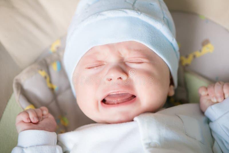 逗人喜爱好一点男婴哭泣的在家说谎在床上 免版税图库摄影