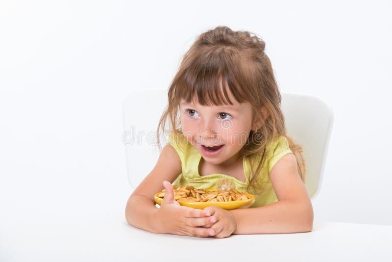 逗人喜爱愉快微笑黄色T恤杉的情感和正面女孩三岁小孩吃谷物剥落的对在白色隔绝的桌 库存图片