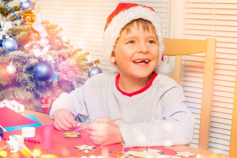 逗人喜爱男孩做在家拥有圣诞节装饰品 免版税库存照片