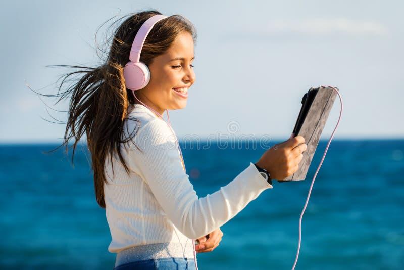逗人喜爱的与耳机和片剂的非离子活性剂女孩听的音乐户外 库存照片