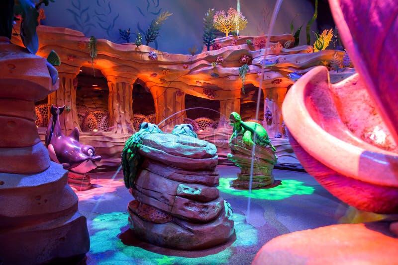 逗人喜爱的乌龟和海豚在迪斯尼海喷洒水 免版税库存图片
