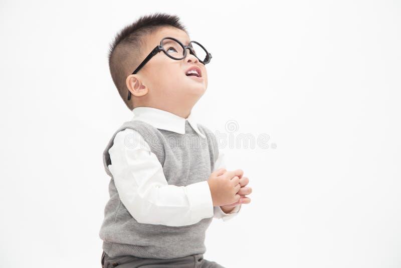 逗人喜爱的亚洲小男孩佩带的白色衬衫、灰色在白色背景隔绝的背心和玻璃 库存照片
