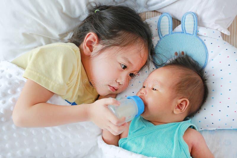 逗人喜爱的亚裔从瓶的姐妹哺养的牛奶说谎在床上的新生儿的 免版税库存图片