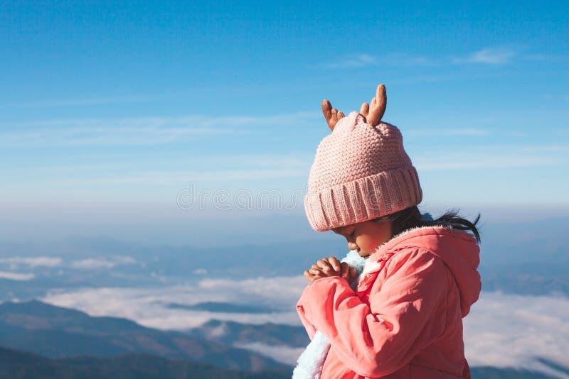 逗人喜爱的亚裔做在祷告的儿童女孩佩带的毛线衣和温暖的帽子被折叠的手在美好的薄雾和山背景中 库存照片
