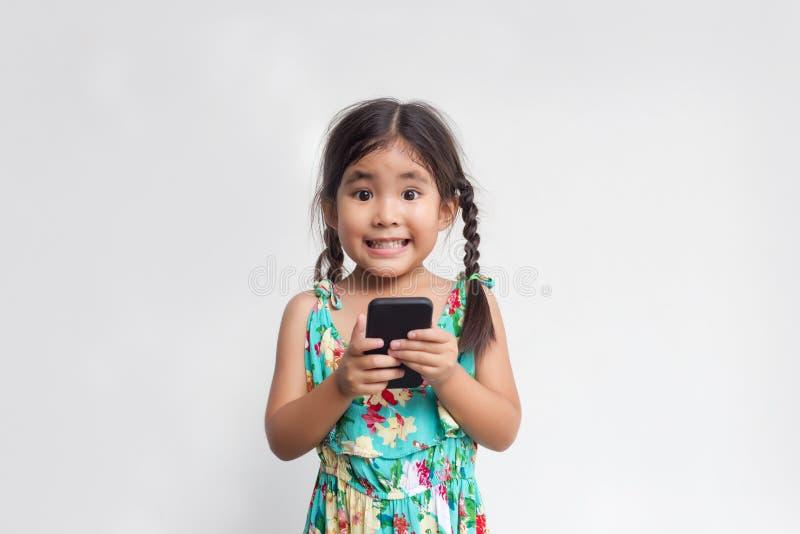 逗人喜爱的亚裔女孩愉快的微笑和举行手机 免版税库存照片