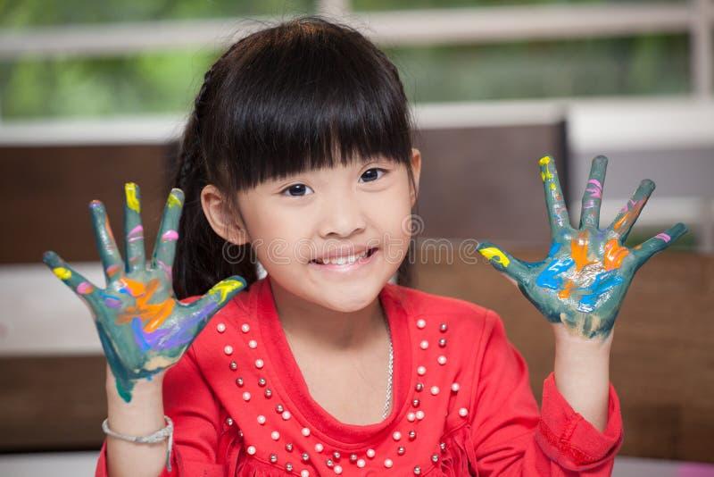 逗人喜爱的亚裔女孩用在油漆的手,在教室学校概念-显示被绘的手棕榈的愉快的孩子在幼儿园 库存图片