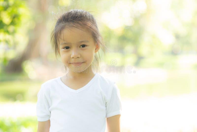 逗人喜爱的亚裔女孩的画象面孔和儿童幸福和乐趣在公园在夏天 免版税库存照片