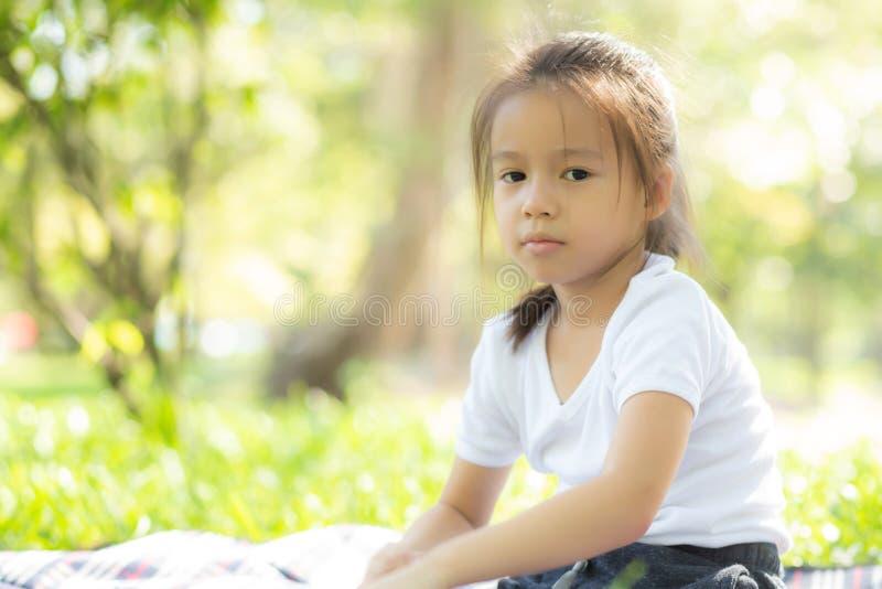 逗人喜爱的亚裔女孩的画象面孔和儿童幸福和乐趣在公园在夏天 库存图片