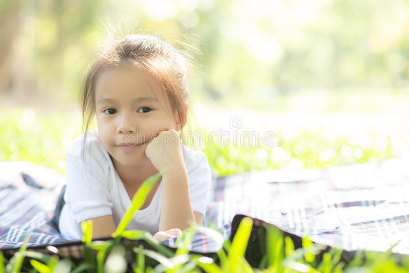 逗人喜爱的亚裔女孩的画象面孔和儿童幸福和乐趣在公园在夏天 免版税库存图片