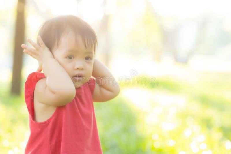 逗人喜爱的亚裔女孩的画象面孔和儿童幸福和乐趣在公园在夏天 库存照片
